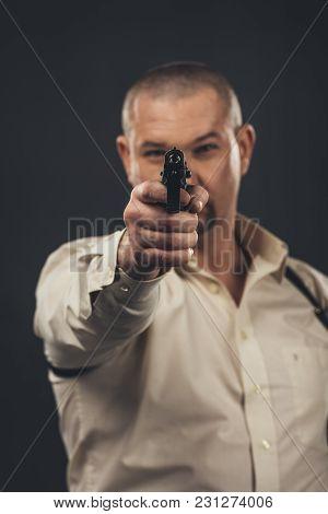 Dangerous Man Aiming Gun At Camera Isolated On Black
