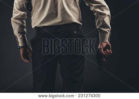 Cropped Shot Of Man Holding Gun In Hand