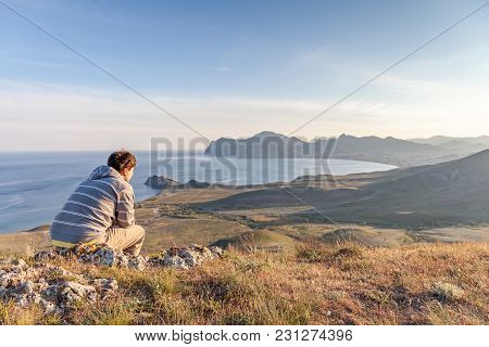 Man Sitting On A Rock On A Hill Above The City Meditating And Watching The Sunset - Horizontal