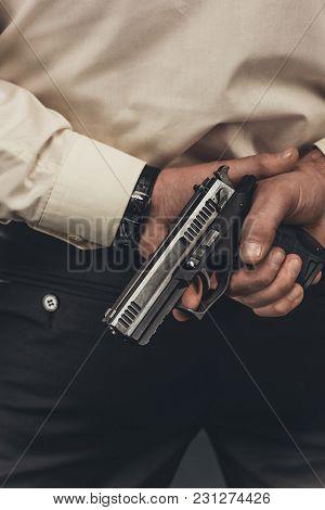 Cropped Shot Of Man In Shirt Holding Gun Behind Back