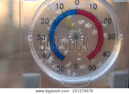 Round Window Thermometer With Snowflakes On It