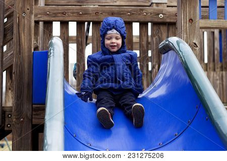 Happy Two Years Toddler On The Children's Slide. Kids Playground
