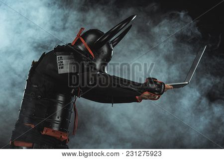 Side View Of Armored Samurai Holding Laptop On Dark Background With Smoke