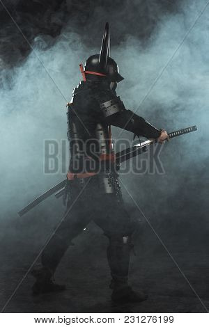Side View Of Samurai Taking Out His Katana On Dark Background With Smoke
