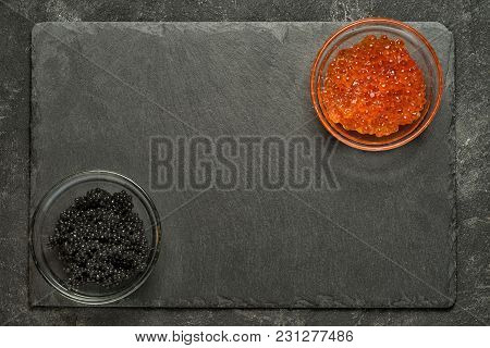 Red Salmon And Black Stugeon Caviar In The Opposit Corners Of Black Stone Board On A Black Table, To