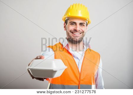 Portrait Of Architect Handing Lunch Box And Smiling
