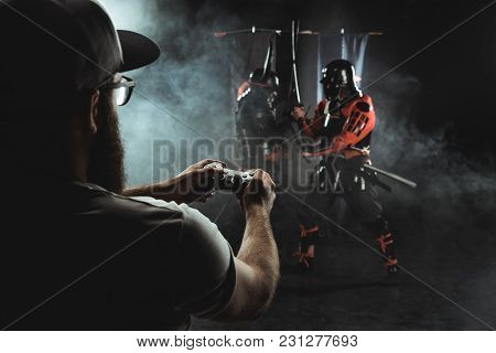 Mature Man In Cap Playing Samurai Fighting With Gamepad In Real Life