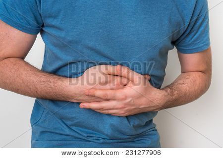 Man With Stomach Pain Is Holding His Aching Belly - Body Pain Concept