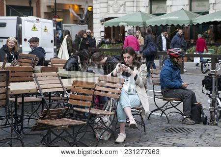 London - September 27, 2016 Women Buried In The Phone, Waiting For The Friend Around Covent Garden