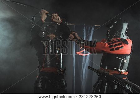 Armored Samurai Fighting With Swords In Front Of Clan Symbols On Flags