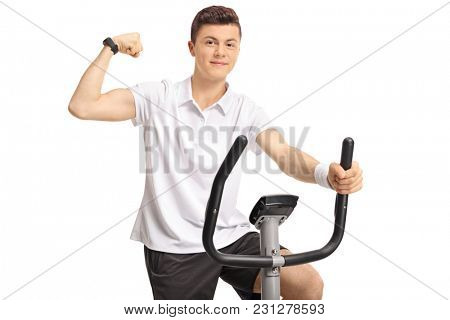 Teenage boy riding an exercise bike and flexing his biceps isolated on white background