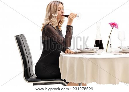 Young woman seated at a restaurant table drinking wine isolated on white background