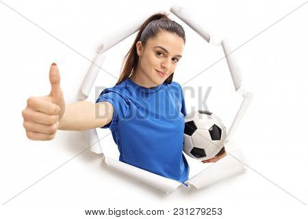 Female soccer player breaking through paper and making a thumb up sign