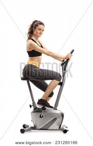 Fitness woman riding an exercise bike and looking at the camera isolated on white background