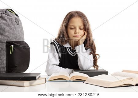 Schoolgirl seated at a table studying unwillingly isolated on white background