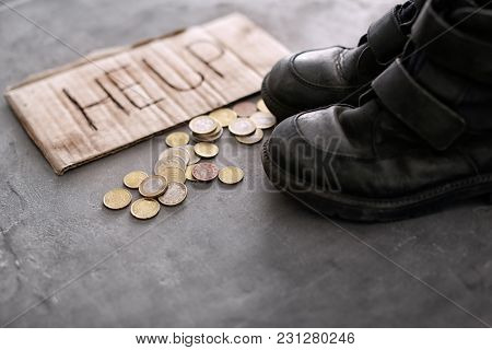 Old shoes, coins and piece of cardboard with word HELP on grey background. Poverty concept