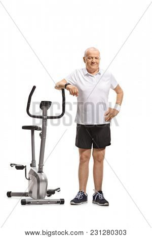 Full length portrait of a mature man leaning on an exercise bike isolated on white background