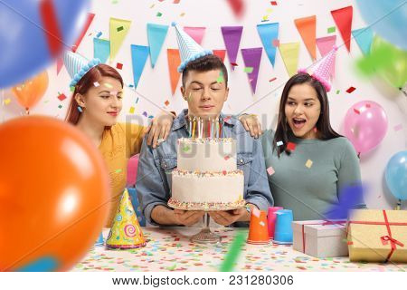 Teenagers with party hats and a cake celebrating a birthday