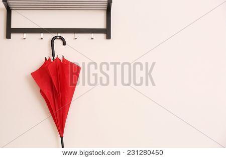 Stylish red umbrella hanging on wall indoors