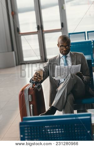 Handsome Young Businessman Waiting For Flight At Airport Lobby