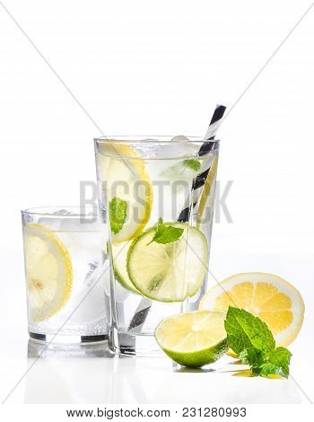 Glass Of Lemonade With Lemon, Lime And Mint On White Background