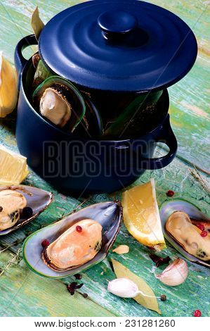 Fresh Boiled Green Mussels With Spices And Lemon In Dark Saucepan With Pan Cover Closeup On Green Wo