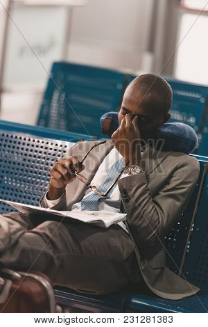 Sleepy Businessman With Travel Pillow Waiting For Flight At Airport Lobby