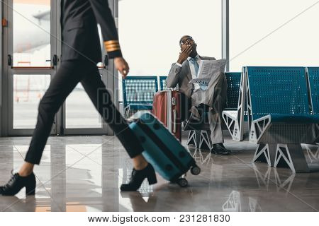 Businessman Waiting For Flight At Airport Lobby While Female Pilot Passing By