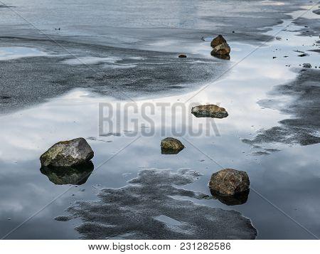 Stones Lying On The Melting Ice Of A Frozen River, Neue Donau Vienna Austria