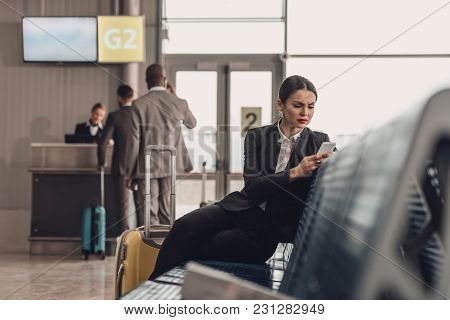 Young Businesswoman Waiting For Plane At Airport Lobby And Using Smartphone