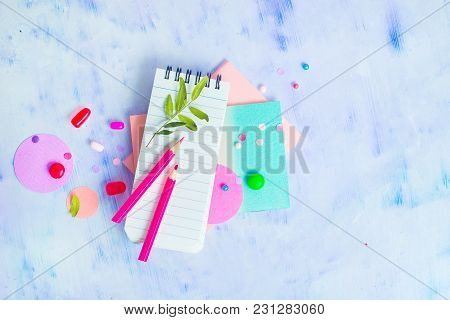 Lined Notepad With Colorful Pencils, Sweets And Pink Macaron Cookie On A Light Background With Copy