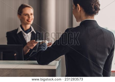 Rear View Of Businesswoman Giving Ticket To Staff At Airport Check In Counter