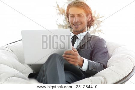 successful businessman with laptop sitting in a large comfortabl