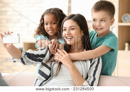 Young woman taking selfie with little kids indoors. Child adoption