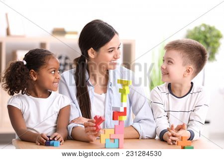 Young woman playing with little kids indoors. Child adoption