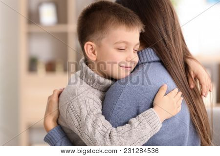 Woman hugging little boy indoors. Child adoption