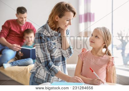 Little girl with mother doing homework at home