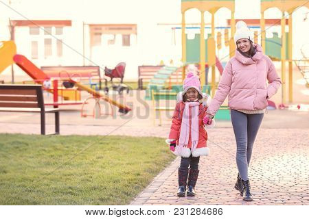 Young woman with little African-American girl outdoors. Child adoption