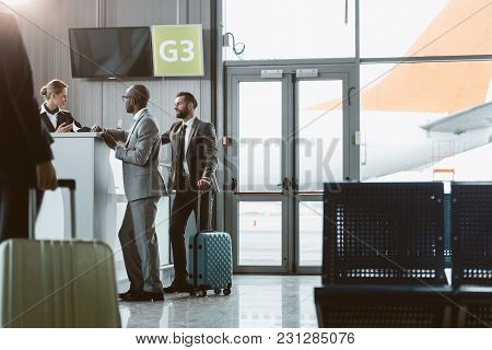 Businessmen Standing At Airport Reception To Buy Tickets While Colleague Walking To Them