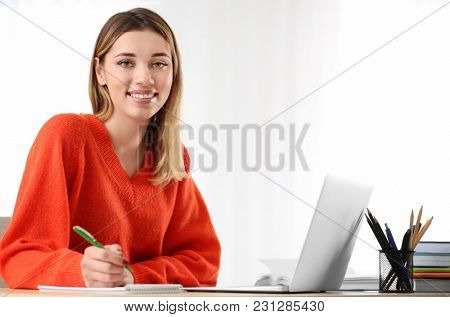 Pretty student with laptop studying at table indoors