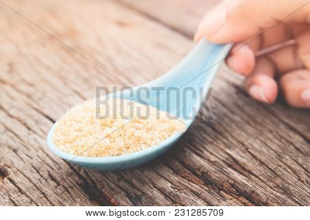 Woman Hand Holding Spoon With Brown Sugar, Unhealthy And Diet Concept