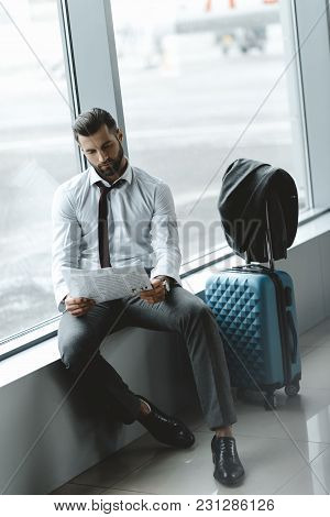 Handsome Businessman Reading Newspaper While Waiting For Flight At Airport Lobby