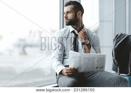 Handsome Young Businessman Through Window While Waiting For Flight At Airport Lobby
