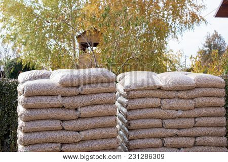 Two Big Piles With Sacks With Biomass In Front Yard