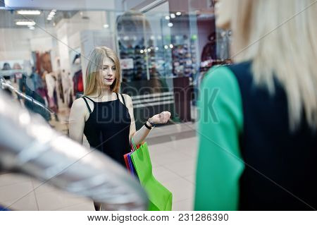Girl With Shopping Bags In The Mall Looking On Mannequins In The Show-window.