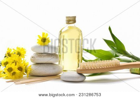 Set of yellow Chrysanthemum daisies and massage oil , stacked stones, brush, bamboo leaf