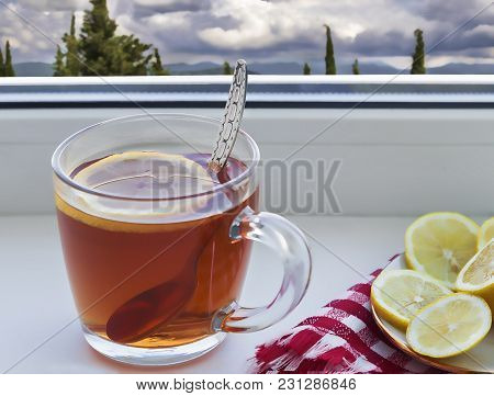 On The Windowsill Is A Cup Of Tea, Next To The Saucer Lemon.