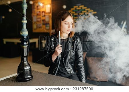 Business Girl Smokes A Hookah After A Hard Day In The Interior Of The Bar