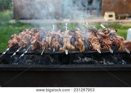Shashlik Or Shashlyk Preparing On A Barbecue Grill Over Charcoal. Grilled Cubes Of Pork Meat On Meta