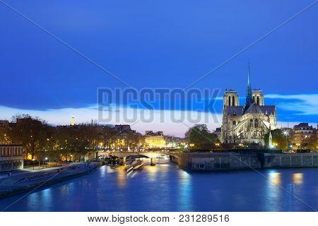 Notre Dame Cathedral On Ile De La Cite And Pont De Archeveche Bridge Over The Seine River, Paris, Fr
